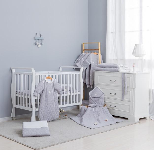 Habitación simple, blanca para bebés con cuna y alfombra.