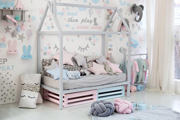 Habitación vacía y acogedora para niños con una pared blanca con pegatinas, juguetes, una cama con almohadas. interior escandinavo de una habitación infantil. cama de madera en forma de casa con juguetes y una manta. jardín de infancia