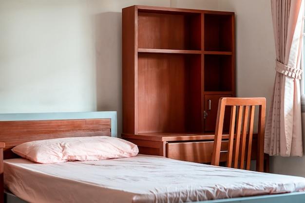 Habitación vacía del dormitorio de estudiantes en la universidad, albergue interior limpio