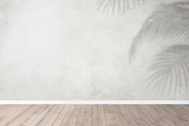 Habitación vacía con pared gris y sombra de hojas tropicales