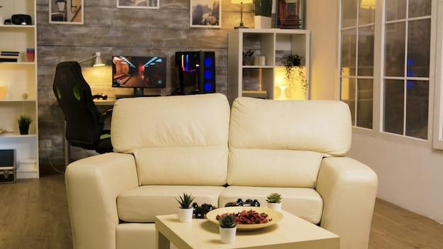 Habitación vacía con sofá en el medio y computadora de juego en el fondo.