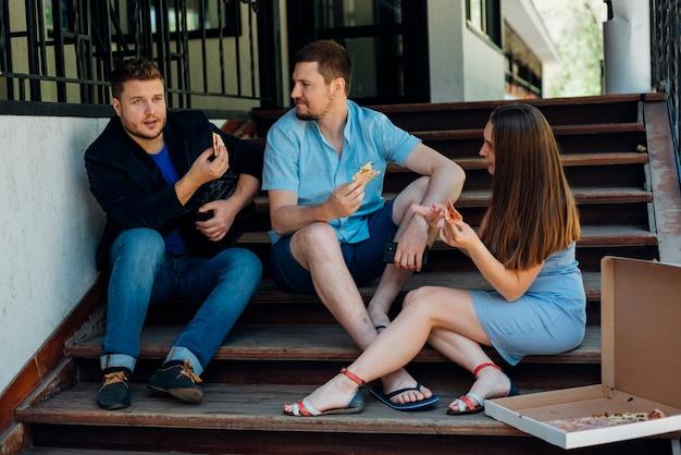Habladores amigos comiendo pizza y sentados en las escaleras