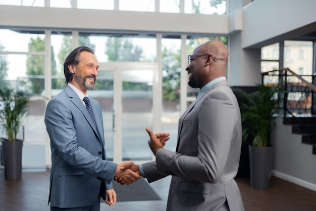 Hablando con un colega. empresario de pelo gris sonriendo mientras habla con su colega en la oficina