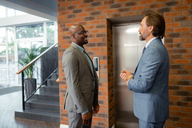 Hablando con un colega. empresario de piel oscura sonriendo mientras habla con un colega de pie cerca del ascensor