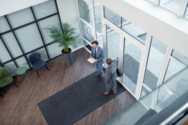 Hablando con empresarios. colega de piel oscura hablando con empresarios y yendo a la reunión
