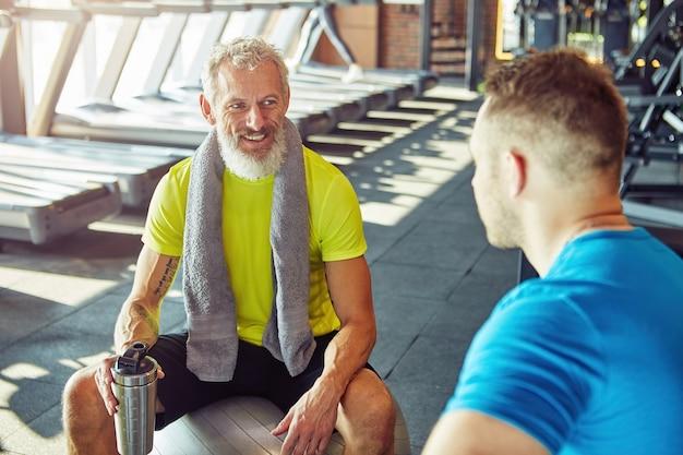 Hablando de un hombre de mediana edad positivo de descanso en ropa deportiva sosteniendo una botella de agua y hablando con