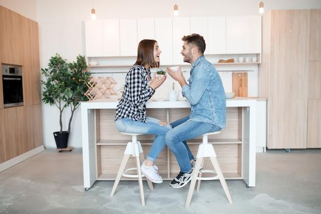 Hablando joven feliz y mujer en la cocina, desayuno, pareja juntos en la mañana, sonriendo, tomando té