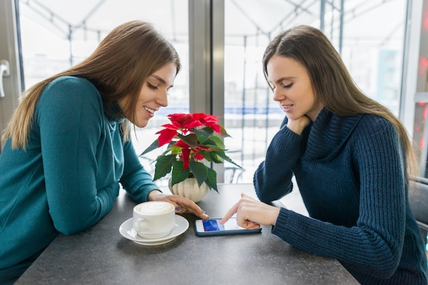 Hablando de mujeres jóvenes, niñas sentadas en la cafetería de invierno sonriendo y hablando con un teléfono inteligente