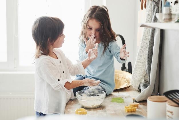 Hablando durante el proceso. amigos preescolares que aprenden a cocinar con harina en la cocina blanca