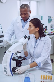 Hablando de proyecto. científica experimentada y decidida que trabaja con un microscopio y habla sobre el trabajo con su colega.