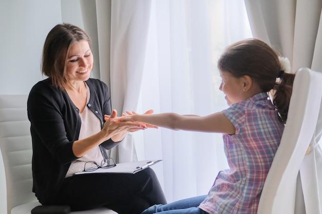 Hablando de psicoterapeuta de niña y mujer en la oficina cerca de la ventana