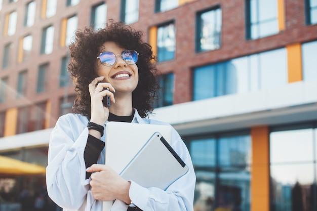 Hablando por teléfono, mujer de negocios caucásica con cabello rizado y anteojos está mirando a la cámara mientras sostiene una computadora portátil