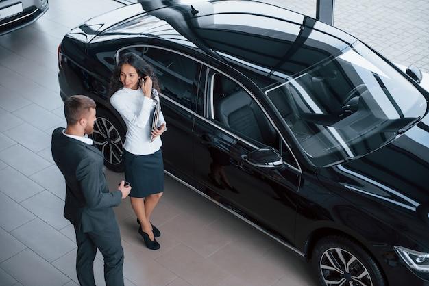 Hablando de ese vehículo nuevo. clienta y empresario barbudo con estilo moderno en el salón del automóvil