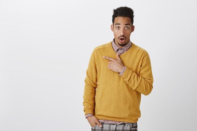 Hablar con un amigo chismes impactantes sobre un compañero de clase. atractivo estudiante afroamericano con peinado afro en jersey amarillo, dejando caer la mandíbula de la sorpresa, apuntando a la esquina superior izquierda
