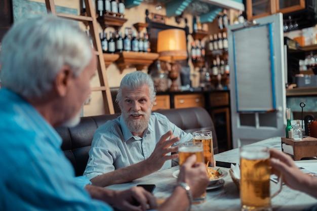 Hablar con amigos. hombre canoso barbudo hablando con amigos mientras bebe cerveza