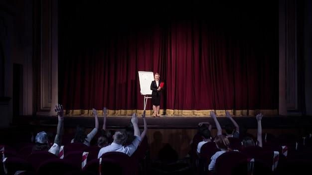 Hablar con la audiencia. oradora femenina dando presentación en el salón del taller. centro de negocios. vista trasera de los participantes en audiencia. evento de conferencia, formación. educación, reunión, concepto de negocio.