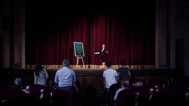Hablar con los estudiantes. oradora femenina dando presentación en el salón del taller. centro de negocios. vista trasera de los participantes en audiencia. evento de conferencia, formación. educación, reunión, concepto de negocio.