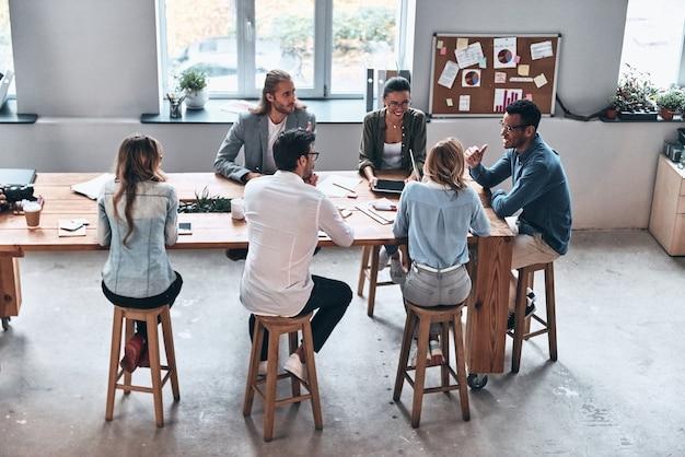 Hablar de nuevas ideas. vista superior de los jóvenes modernos que trabajan juntos mientras están sentados en la oficina