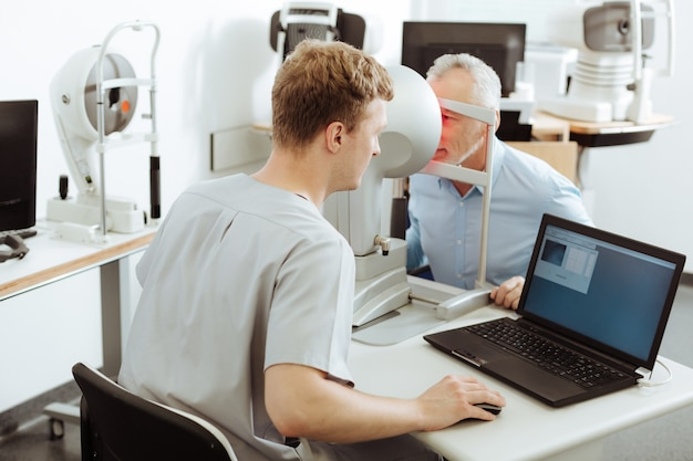 Hablar con el paciente. oftalmólogo profesional de pelo oscuro vistiendo uniforme hablando con el paciente