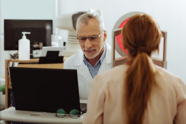 Hablar con el paciente. terapeuta ocular de pelo gris con bata de laboratorio blanca hablando con su paciente