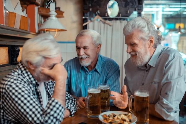 Hablar de partido de fútbol. pensionistas canosos alegres discutiendo el partido de fútbol en el pub