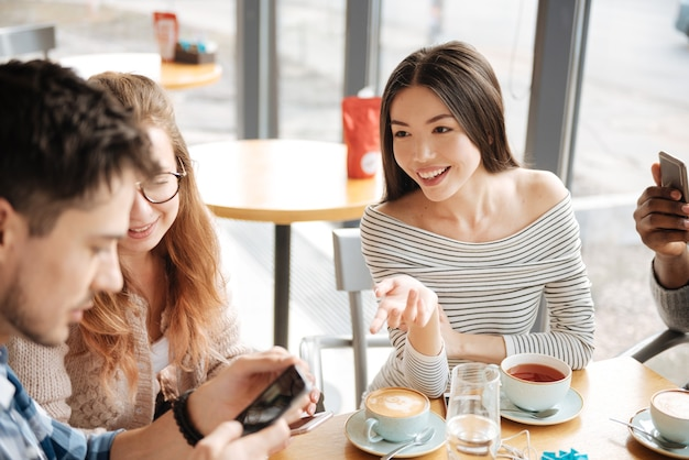 Hablar de las redes sociales. la muchacha asiática sonriente joven está gesticulando a sus amigos en el café usando teléfonos inteligentes.