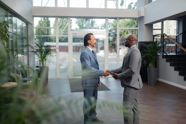 Hablar de su reunión. dos hombres de negocios exitosos discutiendo su reunión de pie en la oficina
