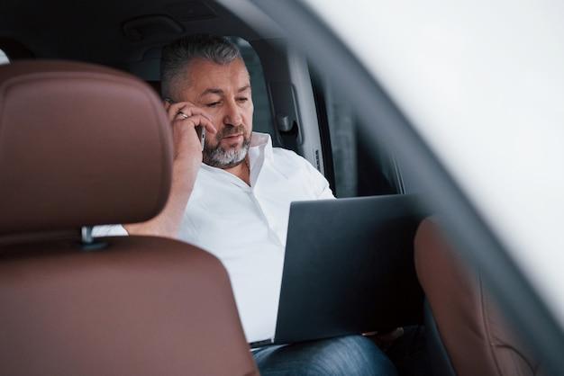 Hablar por teléfono. trabajando en la parte trasera del coche usando una computadora portátil de color plateado. hombre de negocios mayor