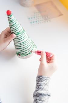 Hacer árbol de navidad. proyecto original de arte infantil. concepto de bricolaje. instrucciones paso a paso. enfoque selectivo hacer decoración de juguetes de navidad. feliz navidad y feliz año nuevo decoración. hecho a mano