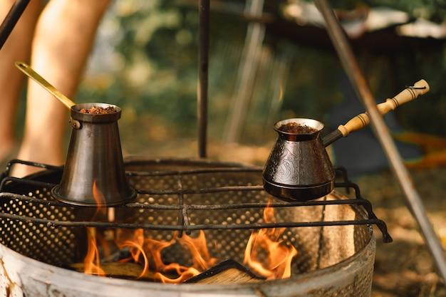 Hacer café en la hoguera hacer café o té en el fuego del equipamiento turístico de la naturaleza