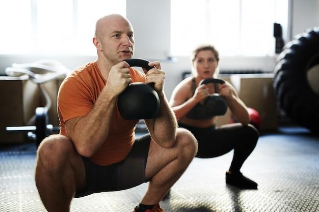 Hacer ejercicio de sentadillas con pesas rusas