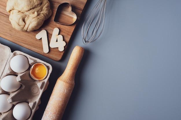 Hacer galletas para el día de san valentín, endecha plana, vista superior, espacio de copia. varios ingredientes, rodillo, masa, huevos, números 14, batir sobre un fondo gris, diseño sobre un fondo gris.