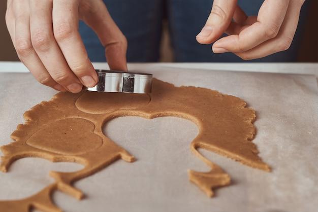 Hacer galletas de jengibre en forma de corazón para el día de san valentín. cortador de galletas de uso de mano de mujer. concepto de comida de vacaciones