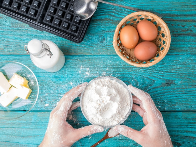 Hacer gofres en casa: plancha para gofres, masa en un tazón e ingredientes: leche, huevos y harina.