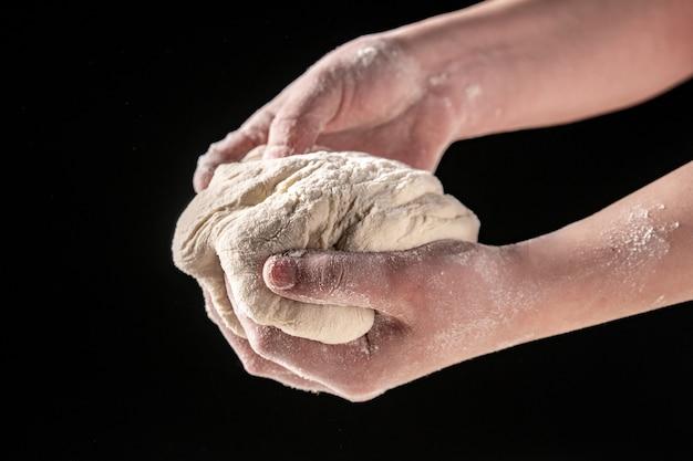Hacer masa por manos femeninas en la panadería, fondo negro