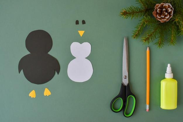 Hacer un pingüino con papel de colores. paso 2. recorta las partes del pingüino.