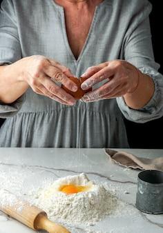 Hacer pizza, mano de mujer trabajando con masa y harina