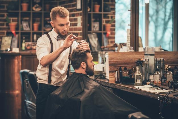 Hacer que el cabello luzca mágico. joven barbudo cortarse el pelo por peluquero