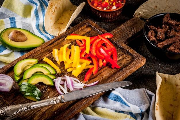 Hacer tacos mexicanos de cerdo con verduras y salsa