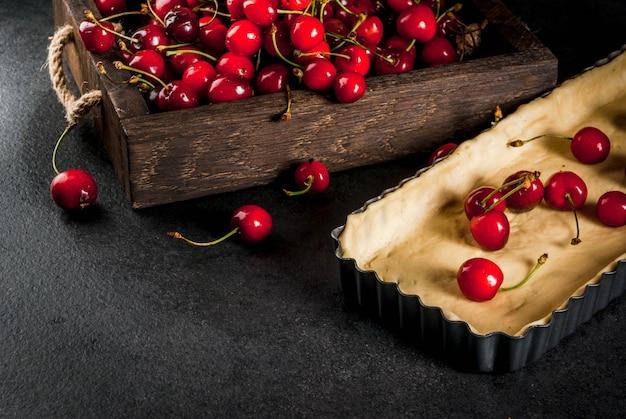 De hacer una tarta de cerezas. cerezas frescas en una bandeja de madera rústica, una forma para hornear con una masa. en una mesa de cocina negra copyspace