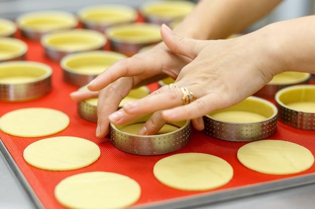 Hacer tartas dulces o saladas y quiche. cocina casera francesa nacional. hecho a mano. entrenamiento de cocina. el cocinero llena la fuente para hornear con el relleno. cortar los rellenos para tarta y quiche.