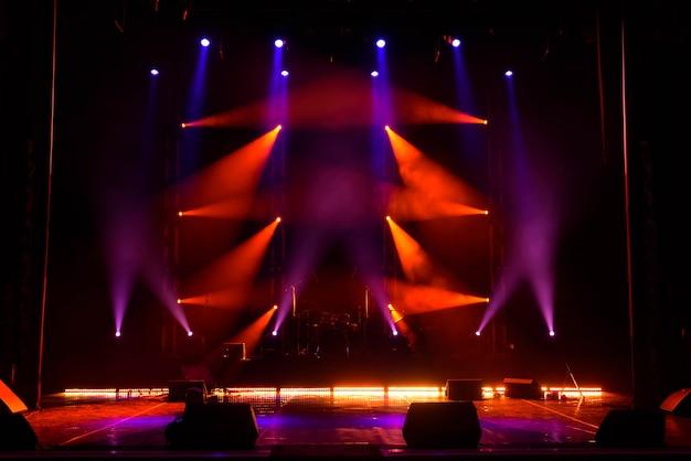 Haces de luces en el escenario con instrumentos musicales