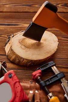 Hacha sobre muñón, cinta métrica y tornillo de banco, mesa de madera, vista superior. instrumento profesional, equipo de carpintero, herramientas de carpintero.