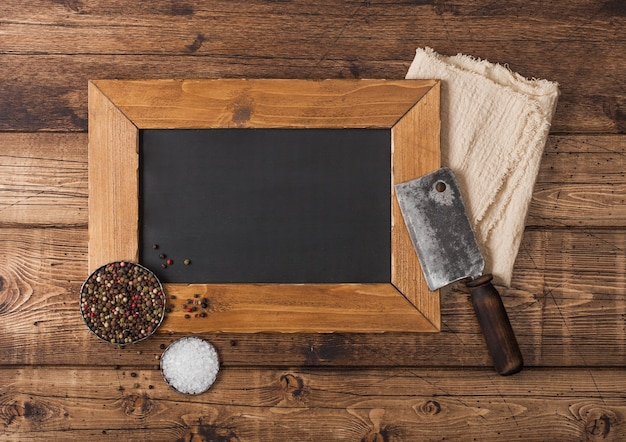 Hacha vintage para carne con tablero de visualización de menú con sal y pimienta sobre fondo de madera.