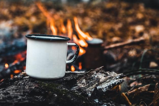 Haciendo café en la hoguera. haga café o té en el fuego de la naturaleza. fuego quemado. un lugar para el fuego. cenizas y carbón.