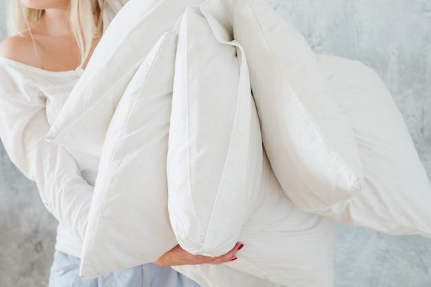 Haciendo la cama. concepto de tareas de la mañana. mujer sosteniendo montón de almohadas