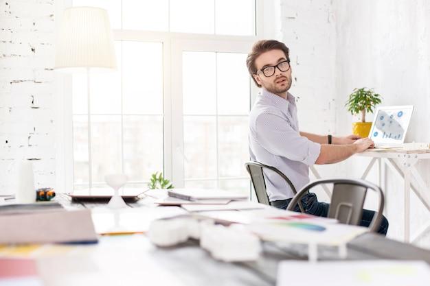 Haciendo mi mejor esfuerzo. determinado empresario de pelo oscuro sentado en la mesa y trabajando en su computadora portátil