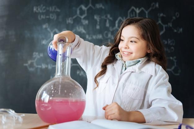 Haciendo todo lo posible por una excelente nota. niño alegre diligente hábil sentado en el laboratorio y disfrutando de la clase de química mientras participa en el experimento de microbiología y usa bombilla