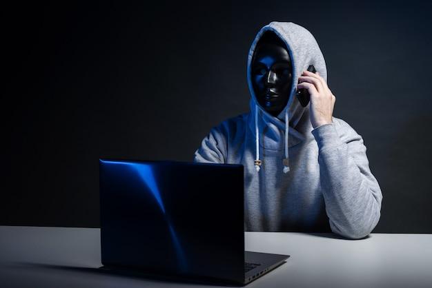 Hacker anónimo en programador de máscara usa una computadora portátil y habla por teléfono para hackear el sistema en la oscuridad. el concepto de ciberdelito y base de datos de piratería