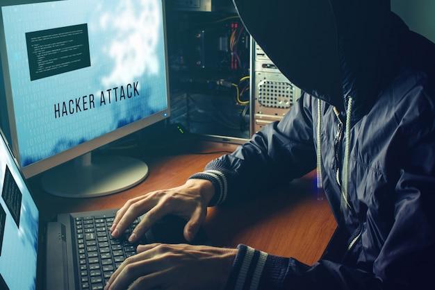 Hacker anónimo sin rostro en la oscuridad, rompe el acceso